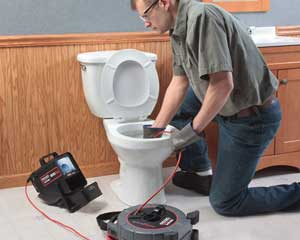 Todd is using a video camera to check a clogged toilet